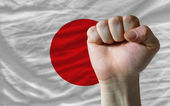 Hard fist in front of japan flag symbolizing power — Stock Photo