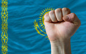 Hard fist in front of kazakhstan flag symbolizing power — Stock Photo