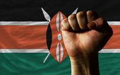 Hard fist in front of kenya flag symbolizing power — Stock Photo