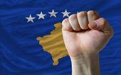 Hard fist in front of kosovo flag symbolizing power — Stock Photo