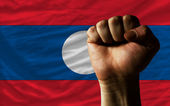 Hard fist in front of laos flag symbolizing power — Stock Photo