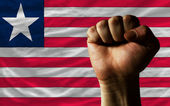 Hard fist in front of liberia flag symbolizing power — Stock Photo