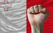 Hard fist in front of malta flag symbolizing power — Stock Photo