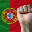Hard fist in front of portugal flag symbolizing power — 图库照片