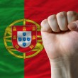 Hard fist in front of portugal flag symbolizing power - Stock Photo