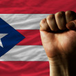 Hard fist in front of puertorico flag symbolizing power - Stock Photo