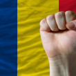 Hard fist in front of romania flag symbolizing power - Stock Photo