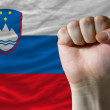 Hard fist in front of slovenia flag symbolizing power — Stock Photo