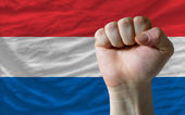 Hard fist in front of netherlands flag symbolizing power — Stock Photo