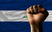 Hard fist in front of nicaragua flag symbolizing power — Stock Photo
