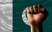 Hard fist in front of pakistan flag symbolizing power — Stock Photo
