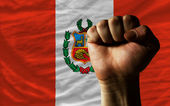 Hard fist in front of peru flag symbolizing power — Stock Photo