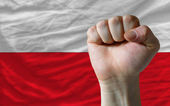 Hard fist in front of poland flag symbolizing power — Stock Photo