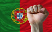 Hard fist in front of portugal flag symbolizing power — Stock Photo