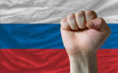 Hard fist in front of russia flag symbolizing power — Stock Photo