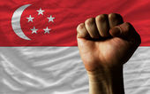 Hard fist in front of singapore flag symbolizing power — Stock Photo