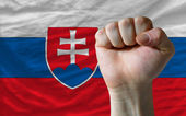 Hard fist in front of slovakia flag symbolizing power — Stock Photo