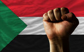 Hard fist in front of sudan flag symbolizing power — Stock Photo