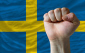 Hard fist in front of sweden flag symbolizing power — Stock Photo