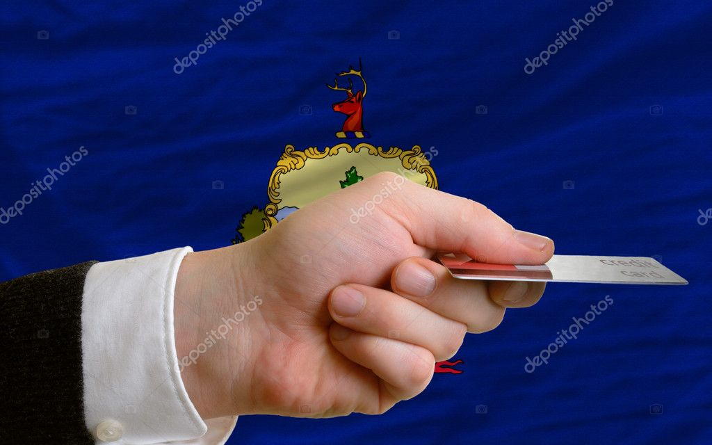 Man stretching out credit card to buy goods in front of complete wavy national flag of american state of vermont — Stock Photo #11200121