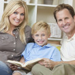 Happy Family Sitting on Sofa Reading A  Book - Stock Photo