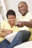 Afroamerikaner paar Essen Popcorn vor dem Fernseher — Stockfoto