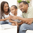 African American Family Using Laptop Computer - Stock Photo