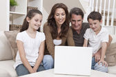Happy Family Using Laptop Computer on Sofa at Home — Stock Photo