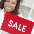 African American Woman Holding Sale Sign - Stock Photo