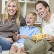 Happy Family Sitting on Sofa Laughing Watching Television — Stock Photo #11458026