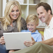 Stock Photo: Happy Family Sitting on Sofa Using Laptop Computer