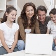 Happy Family Using Laptop Computer on Sofa at Home - Stock Photo