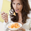 Brunette Woman Eating Melon At Home on Sofa — Stock Photo #11458414
