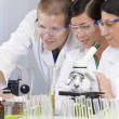 Interracial Team of Scientists In Laboratory With Laptop - Stock Photo
