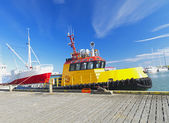 Bright yellow tug boat in the harbor — Stock Photo