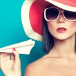 Summer girl holding an airplane — Stock Photo