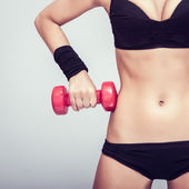 Athletic body with dumbbells close-up — Stock Photo