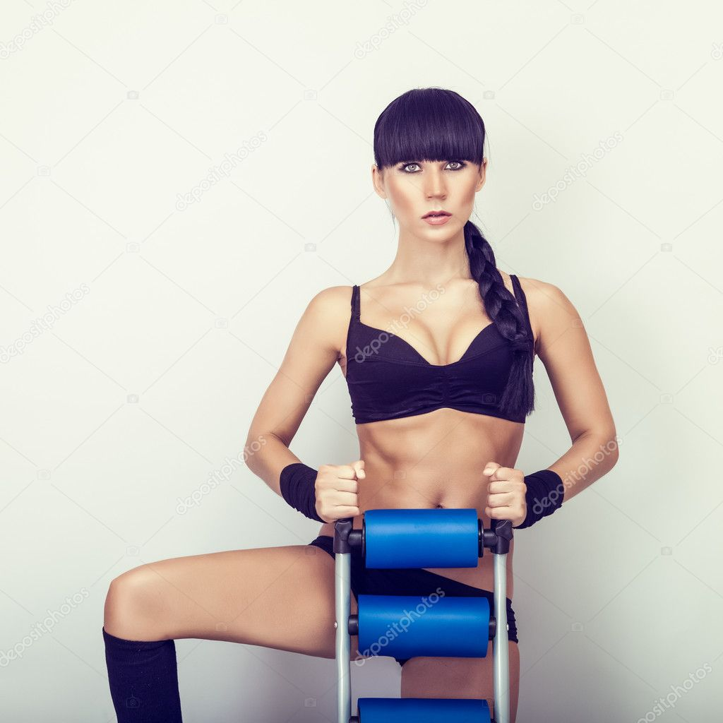 Beautiful woman with athletic trainer press — Stock Photo #11695548