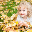 Child lying on yellow leaves — Stock Photo #10909804
