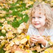Stock Photo: Child lying on yellow leaves