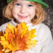 Happy smiling child holding yellow maple leaves — Stock Photo