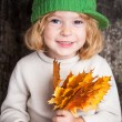 Kid with yellow maple leaves — Stock Photo