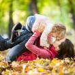 Woman with child having fun in autumn park — Zdjęcie stockowe #10909874
