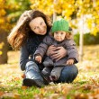 Woman with child having fun in autumn — Foto Stock