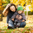 Woman with child having fun in autumn — Stok fotoğraf