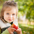 Child with apple in autumn park — Stockfoto