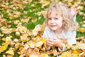 Child lying on yellow leaves — Stok fotoğraf