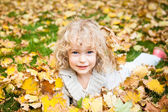 Child lying on autumn leaves — Stok fotoğraf