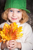 Happy smiling child holding yellow maple leaves — ストック写真