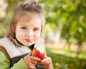 Child with apple in autumn park — Stok fotoğraf